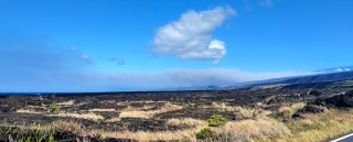 Recent explosive events haven't produced significant ash plumes from the summit, but downwind communities may still experience ashfall when previously erupted ash is remobilized. On authorized permission from Hawai'i Volcanoes National Park, our Unmanned Aircraft Systems crew is conducting gas measurements at Pu'u 'Ō'ō. They snapped this photograph from Chain of Craters Road - a plume of remobilized ash is clearly visible along the horizon. It is rising from the Ka'ū Desert and blowing to the southwest. Photo taken Tuesday, June 26, 2018 courtesy of U.S. Geological Survey