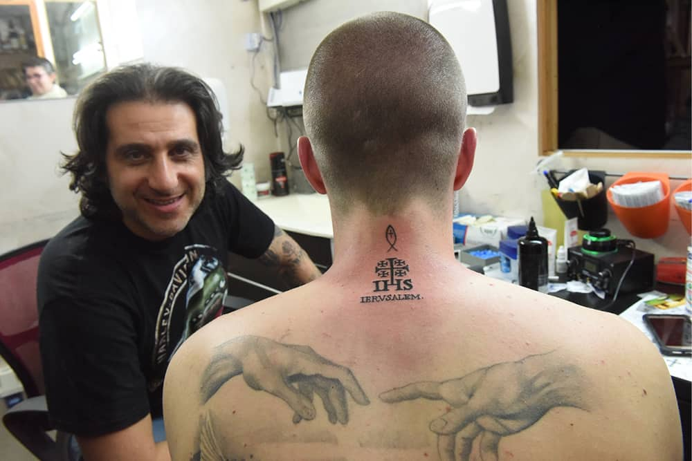 Holy Land pilgrims get tattoos to remember their travels - Hawaii ...