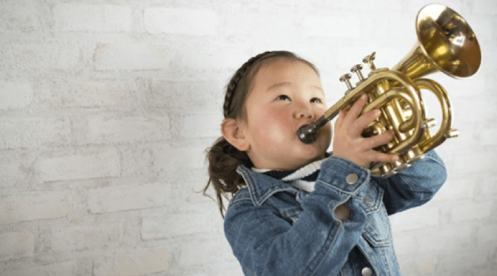 A young girl plays a horn instrument