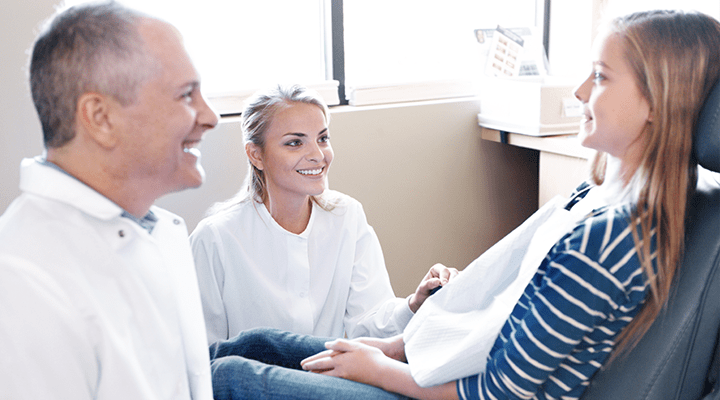 A dentist and his dental assistant make a young female patient laugh in the dental chair.