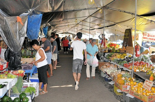 Big Island farmers market set up under large tent, people shopping