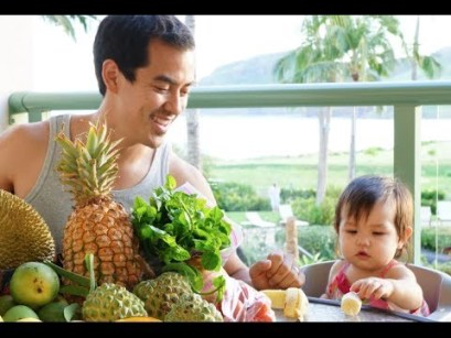 Dad looking at kid over a pile of organic produce from a Kauai farmers market