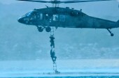 A UH-60 Black Hawk assigned to Company B, 2nd Battalion, 25th Aviation Regiment, 25th Combat Aviation Brigade drops the caving ladder for Navy divers with the U.S. Navy SEAL Delivery Vehicle Team 1, Naval Special Warfare Group 3 for extraction during HELOCAST training with flight crews from the 25th CAB at Marine Corps Air Station Kaneohe Bay June 18.