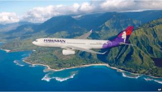 FILE - A Hawaiian Airlines plane flies above Hawaii