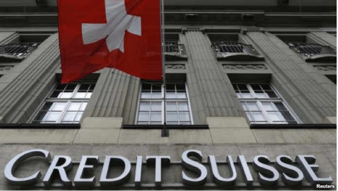 The logo of Swiss bank Credit Suisse is seen below the Swiss flag at a building in the Federal Square in Bern, Switzerland, May 15, 2014.