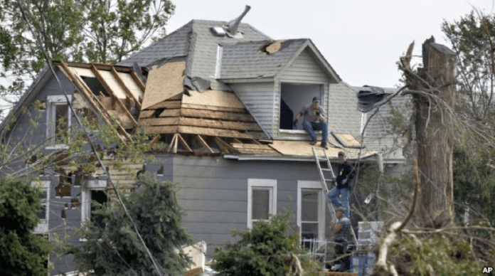 Workers pause while working on house damaged by a tornado in Pilger, Nebraska, June 18, 2014.