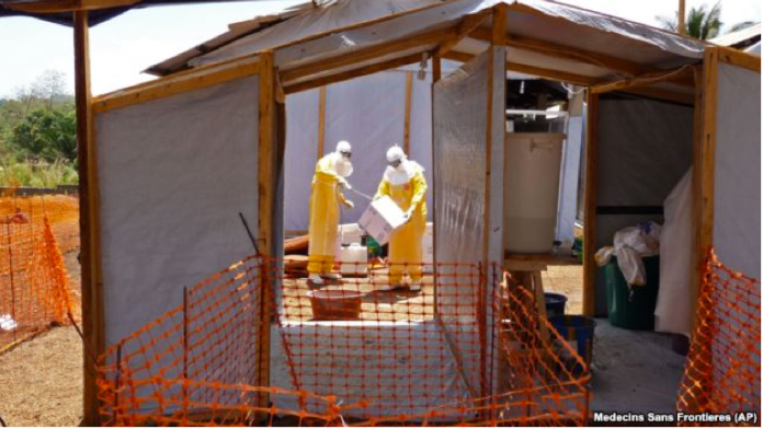FILE - Health care workers from Medecins Sans Frontieres prepare isolation and treatment areas for their Ebola, hemorrhagic fever operations, in Gueckedou, Guinea.