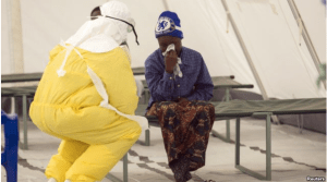 A health worker wearing protective gear attends to a newly admitted suspected Ebola patient in a quarantine zone at a Red Cross facility in Koidu, Kono district in eastern Sierra Leone, Dec. 19, 2014.