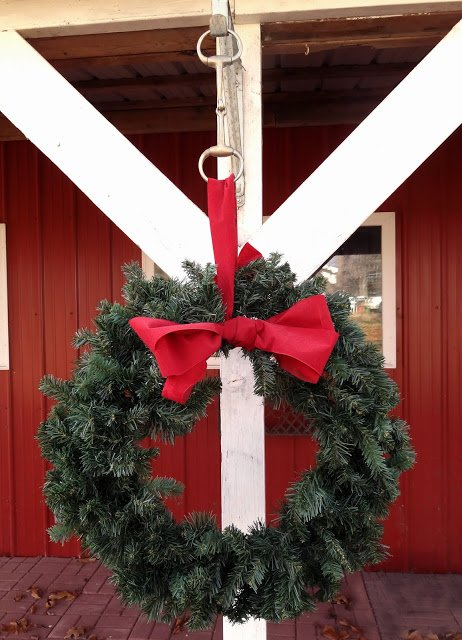christmas wreath hung on stable with horse snaffle bit