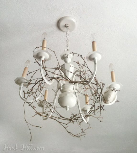 My woodland inspired chandelier upgrade, featuring a wreath of branches and a tiny bird, resting on the chandelier arms.