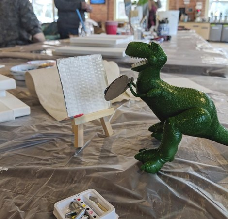 A toy dinosaur stands in front of a blank canvas