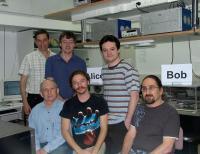 בתמונה: מעבדת המיקרופוטוניקה בפקולטה להנדסת חשמל בטכניון והצוות העורך מחקרים במימוש הצפנה קוונטית. מימין (יושב) פרופ' טל מור מהפקולטה למדעי המחשב. עומדים (משמאל) דר. מתי כץ ולידו פרופ' מאיר אורנשטיין מהפקולטה להנדסת חשמל. פבל גורביץ, אלכס חייט ואלכס פורוצקי הינם חלק מהצוות שינסה לממש את השיטה החדשה.