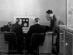 אלן טיורינג (עומד מימין), בריאן פולארד וקית לונסדייל ליד פראנטי סימן 1, מחשב רב-תכליתי שהיה המחשב המסחרי השני. צילום: Courtesy of The University of Manchester, the School of Computer Science