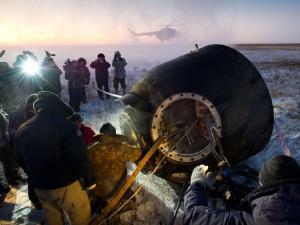 """אנשי התמיכה של סוכנות החלל הרוסית סייעו לאנשי הצוות ה-29 לצאת מחללית הסויוז TMA-02M זמן קצר לאחר הנחיתה ליד העיר אקארליק בקזחסטן. צילום: נאס""""א/ביל אינגלז"""