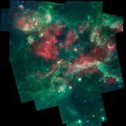 """תמונה באינפרה אדום של איזור יצירת הכוכבים סיגנוס X נצבעה בצבעים מלאכותיים המקודדים לפי אורכי גל. אור ב-3.6 מיקרון צבוע בכחול, אור ב-4.5 מיקרון בכחול-ירוק, 8 מיקרון בירוק ו-24 מיקרון באדום. תמונות אלה צולמו לפני שמשימת שפיצר סיימה את גז הקירור ב-2009, והפכה למשימה """"חמה""""."""