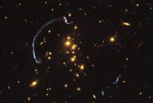 """גלקסיה המרוחקת 10 מיליארד שנות אור כפי שצולמה בסיוע עדשה כבידתית ע""""י טלסקופ החלל האבל"""