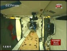 מפקד החללית שנז'ו 9 ג'ינג הייפנג נכנס לתוך מעבדת החלל טיאנגונג 1. צילום: הטלוויזיה הסינית