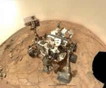 כיתוב: רכב המאדים קיוריוסיטי בצילום עצמי באמצעות מצלמת MAHLI, בעת ששה באיזור סלע משקע שטוח המכונה ג'ון קליין, שם נטל הרובוט את דגימת הקרקע הראשונה באגן מפרץ הסכין הצהוב ב-8 בפברואר 2013 (סול או יום מאדימאי 182) בחלק התחתון הקדמי של הרכב. תצרף התמונות גם כולל חומרי גלם שצולמו בסול 177 - 3 בפברואר 2013 בידי מצלמת הזרוע של הרכב האחראית לרקע. צילום: NASA/JPL-Caltech/MSSS/Marco Di Lorenzo/KenKremer (kenkremer.com).