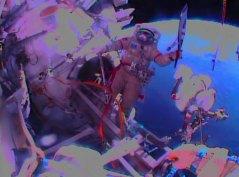 מצלמת הקסדה של הקוסמונאוט סרגיי ריאז'נסקי צילה את עמיתו אולג קוטוב מניף את הלפיד האולימפי מחוץ לתחנת החלל הבינלאומית במהלך הליכת החלל היום (שבת, 9/11/13). צילום: NASA TV