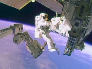 """האסטרונאוט מייק הופקינס רוכב על הזרוע הרובוטית של תחנת החלל הבינלאומית כשהוא סוחב את משאבת האמוניה שמשקלה כ-350 ק""""ג, כאשר התחנה חלפה מעל דרום אמריקה. צילום: NASA TV"""