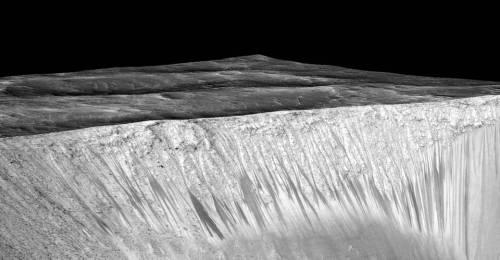 ערוצים כהים וצרים אלה המכונים (SRL) recurring slope lineae נובעים מתוך קירות מכתש גארני על מאדים. הערוצים הכהים כאן מגיעים לאורך של מאות מטרים. ההשערה היא כי נוצרו בידי זרימת מים מליחים על מאדים, כפי שצולמו על ידי החללית MRO. Credits: NASA/JPL/University of Arizona