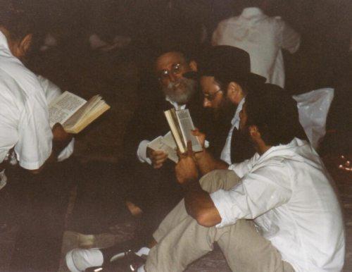 """אמירת קינות ברחבת הכותל, ערב תשעה באב ה'תשס""""ד (2004); ניתן להבחין כי האנשים יושבים על הקרקע, ונמנעים מלשבת על כיסאות מוגבהים - כחלק ממנהגי האבלות. צילום: משתמש Idobi מתוך ויקיפדיה"""