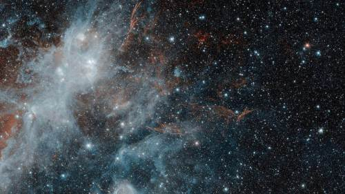 """בתמונה זו, שצולמה במרץ 2010 על ידי טלסקופ החלל שפיצר של נאס""""א ופורסמה השבוע לרגל מלאת 15 שנה לטלסקופ נראים שרידיה של הסופרנובה HBH 3. אורכי גל אינפרא אדום באורך גל של 3.6 מיקרון ממופים בכחול, ואור באורך גל של 4.5 מיקרון מתורגם לצבע אדום. הצבע הלבן של אזור יצירת הכוכבים הוא שילוב של שני אורכי גל, ואילו ה""""חוטים"""" של HBH3 מקרינים רק באורך גל של 4.5 מיקרון. ב - 2016, זיהה טלסקופ קרני הגאמא פרמי של נאס""""א זיהה סיילון של קרינת גאמא שהגיעו מהאזור ליד HBH 3. פליטה זו עשויה להגיע מגז בתוך אחד מאזורי יצירת הכוכבים הסמוכים לסופרנובה שהתנגש עם חלקיקים שנפלטו מהסופרנובה עצמה. צילום: נאס""""א"""