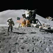 """האסטרונאוט ג'יימס אירווין על רקע דגל ארה""""ב, מודול הירח של אפולו 15, ורכב השטח עליו נסעו במרחבי הירח. צילום: נאס""""א"""
