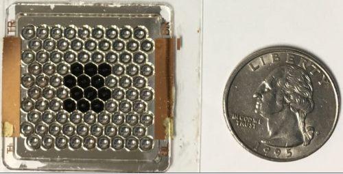 אב-הטיפוס הראשון, מורכב מ-90 מרכזי אור שמש מזעריים, המצולם לאחר הכנסת 12 תאי שמש (משושים שחורים). מטבע של רבע דולר אמריקאי להשוואה.   צילום: אוניברסיטת בן-גוריון בנגב