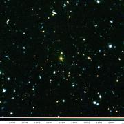 תמונה מורכבת של אשכול הגלקסיות XLSSC 122 בעזרת תמונות מטלסקופ החלל האבל ומהטלסקופ הגדול מאוד של מצפה הכוכבים האירופי. קווי המתאר הלבנים חושפים פליטת רנטגן חזקה שנצפתה על ידי לוויין ה- Multi-Mirror של סוכנות החלל האירופית. (ג'ון וויליס) . באדיבות המחבר
