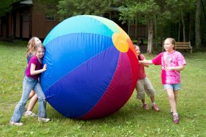 Girl's Summer Camp - Girls Playing with Large Ball Outdoors