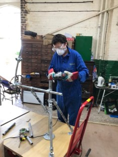 Hazel on the angle-grinder cutting tube lengths