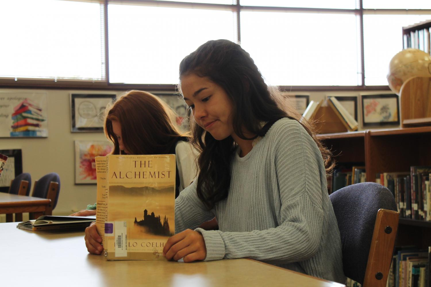 Freshman Rei Hemmer sits in the library reading her summer reading book during her English class.