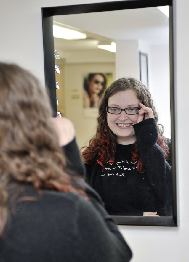 Photo of a woman trying on a pair of eyeglasses.