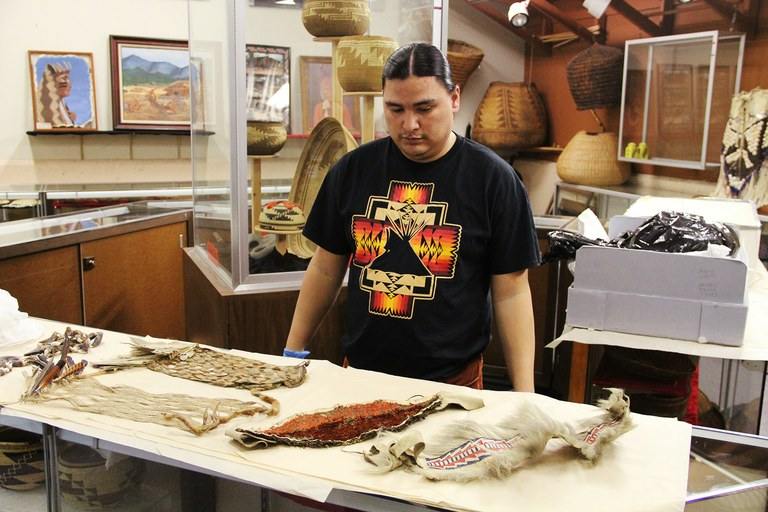 Hoopa Tribal Museum curator Silis-chi-tawn Jackson displays artifacts returned to the tribe by Harvard University's Peabody Museum that were preserved with dangerous chemicals.