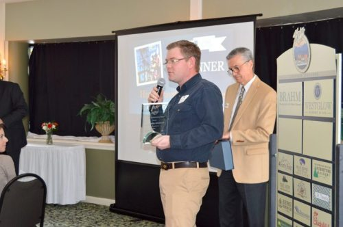 Carson Rivers accepts the chamber's award for commercial construction on behalf of High Gravity Adventures.