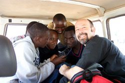 Don Cox of Bald Guy Brew (right) poses with friends he made during a 2001 trip to Rwanda.