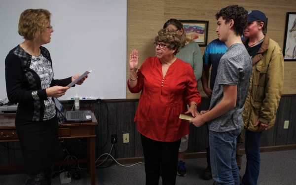 Returning board member Brenda Reese, accompanied by family, is sworn in by N.C. District Judge Rebecca Eggers-Gryder. Reese was later voted the board's vice-chair.