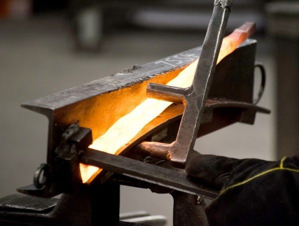 The red hot leg of what will become a drink table base is bent over a jig at the Charleston Forge factory in Boone, NC. All of the company's nearly 300 products are hand built using age-old blacksmithing techniqes. (Photo by Philp Holman/Charleston Forge)