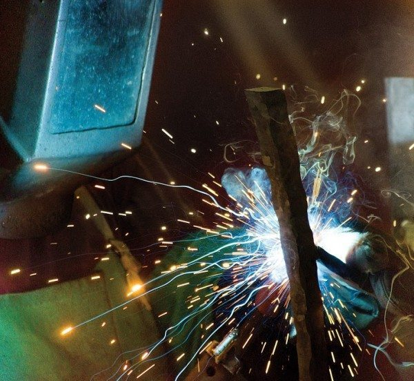 Charleston Forge welder, Toby Richards, fabricates the base of a Metro Drink Table at the company's factory in Boone, NC. Richards, whose son Charlie works as a forger with the company, has worked at Charleston Forge since 1994. (Photo by Philp Holman/Charleston Forge)