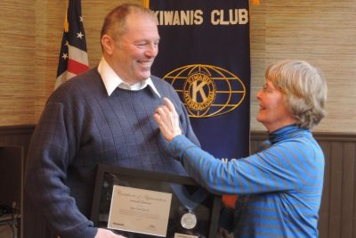 Ann Swinkola pins husband Jim during the Kiwanis meeting where he was recognized with the Centennial Award.