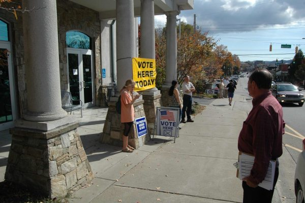 Watauga County Board of Elections official Robert Southwick waits on a voter to fill out a curbside ballot.