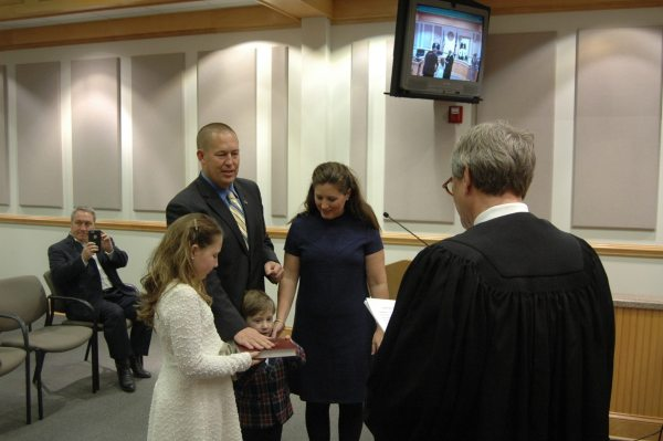 Democrat Commissioner John Welch, with his family by his side, is sworn into office.