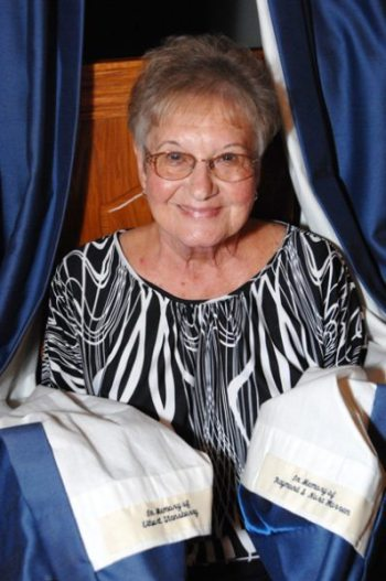 Libby Warren is pictured showing off curtains at Beech Valley Missionary Baptist Church that honor Billy's parents and a longtime church deacon. Photo by Peter W. Morris.