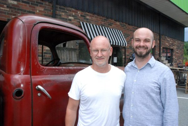 """David Gindlesperger and Steve Zimmerman are pictured with """"Red,"""" a vintage pickup truck who now calls Curiosity Consignment Mega Warehouse home."""