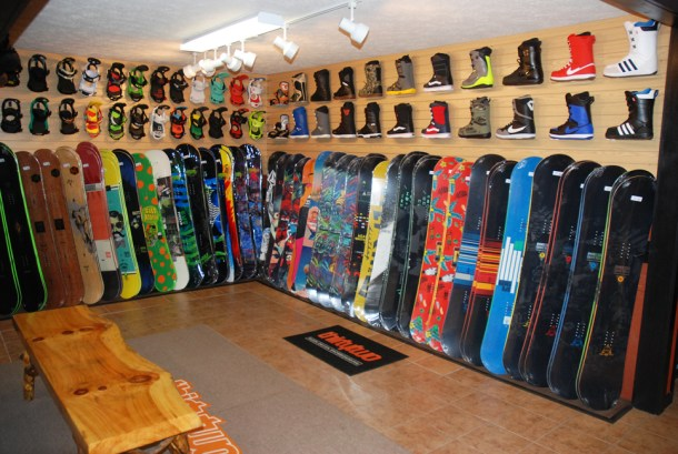 Snowboards and bindings line the walls of the shelve