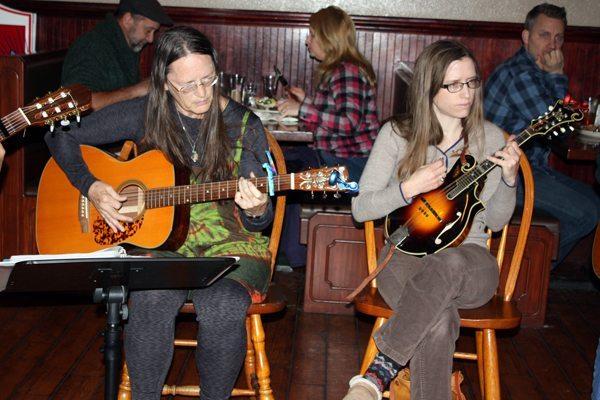 Christine Operario plays guitar and Abbie Crumrine plays the mandolin