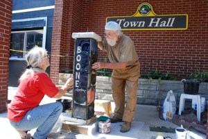 Willie Baucom and Keith Lambert installing a custom AppalCART bus stop marker on West King Street on Thursday, Aug. 2. Photo by Ken Ketchie