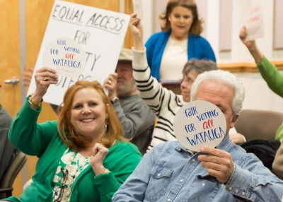 "Watauga County Republican Chair Anne-Marie Yates holds up a sign that says ""Fair Voting for All Watauga"" at a Board of Elections meeting in March. Photo by Lonnie Webster"