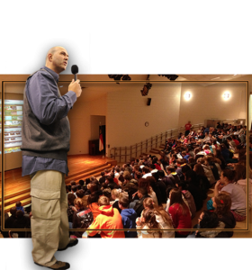 Gabriel standing. In the background is a school assembly. Photo courtesy of Sold Out NC website.